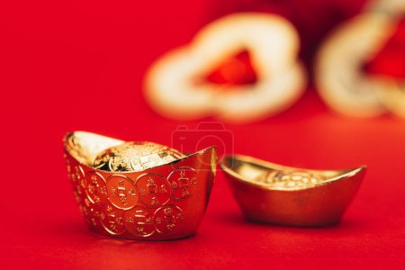 Photo for Close-up shot of chinese golden ingots on red surface - Royalty Free Image