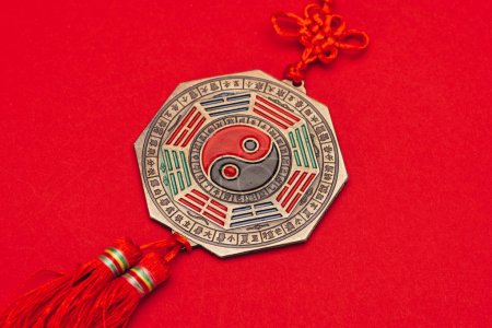 close-up shot of chinese yin and yang talisman on red surface