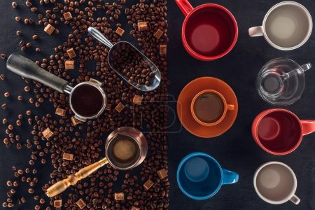 top view of roasted coffee beans, scoop, coffee pot, coffee tamper and cup of coffee with empty cups on black