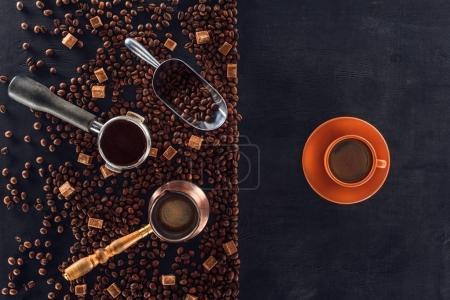 Photo pour Vue de dessus des grains de café torréfiés, cuillère, cafetière, tampon de café et tasse de café sur noir - image libre de droit