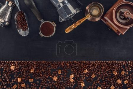 Photo for Top view of roasted coffee beans with brown sugar and various coffee makers and grinders on black - Royalty Free Image