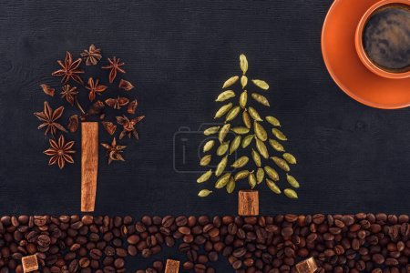 top view of roasted coffee beans with sugar, cup of coffee and trees symbols made from spices on black