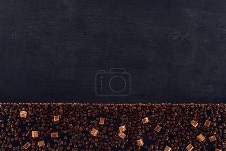 top view of roasted coffee beans with brown sugar on black
