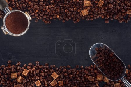 top view of roasted coffee beans with brown sugar, coffee tamper and scoop on black