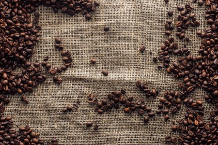 top view of roasted coffee beans on sackcloth with copy space