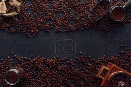 Photo pour Vue de dessus des grains de café torréfiés, sac, moulin à café et scoop sur noir - image libre de droit