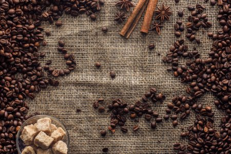 top view of roasted coffee beans with cinnamon sticks, star anise and brown sugar in glass bowl on sackcloth