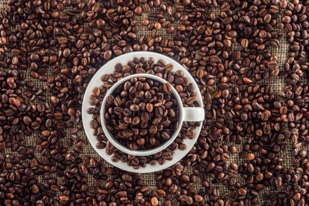 top view of coffee cup and roasted coffee beans on sack clothes