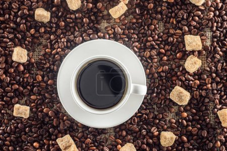 top view of cup of coffee, brown sugar, coffee beans on sack clothes