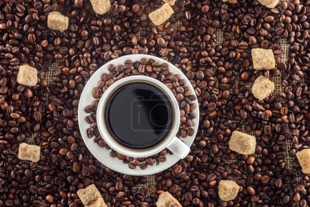 top view of cup of coffee with saucer, roasted coffee beans and brown sugar on sackcloth