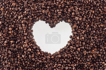 top view of heart made from roasted coffee beans on white
