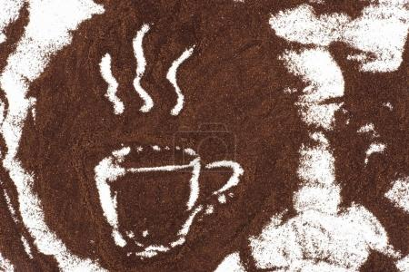 top view of cup of coffee sign drawn in coffee on white