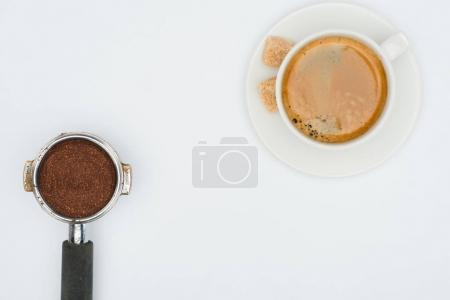 top view of cup of coffee and coffee tamper isolated on white