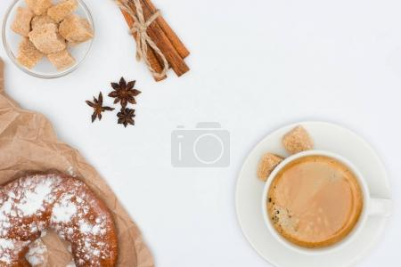 top view of cup of coffee with saucer and brown sugar, pastry, anise stars and cinnamon sticks tied with rope isolated on white