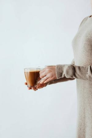 partial side view of woman holding glass cup with coffee isolated on white