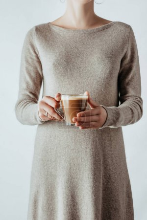 mid section of woman holding glass cup with coffee isolated on white