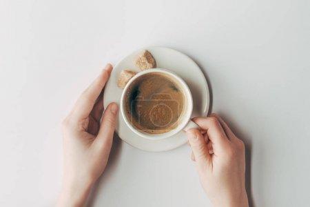 Photo pour Vue de dessus des mains humaines et tasse de café avec du sucre sur blanc - image libre de droit
