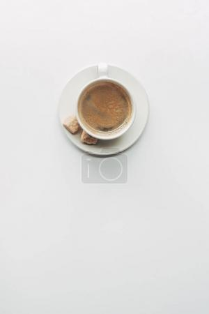top view of cup of aromatic coffee with saucer and brown sugar isolated on white