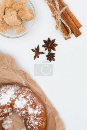 top view of fresh pastry on baking paper, brown sugar in glass bowl, star anise and cinnamon sticks tied with rope on white