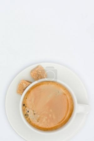Photo for Top view of cup of coffee with saucer and brown sugar isolated on white - Royalty Free Image