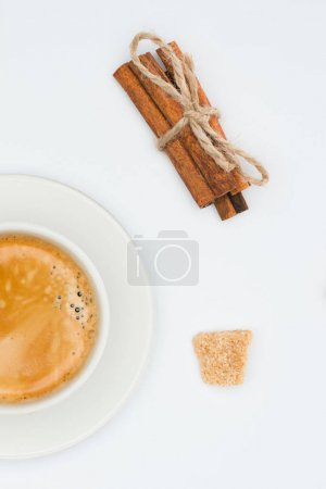 top view of cup of coffee with saucer, brown sugar and cinnamon sticks with rope isolated on white