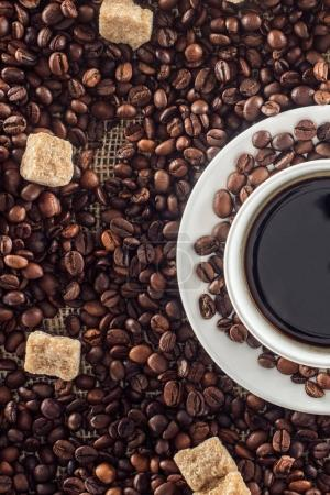 cup of coffee, roasted coffee beans and brown sugar on sackcloth