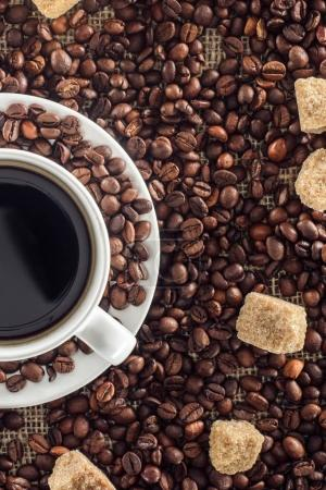 close-up view of cup of coffee, roasted coffee beans and brown sugar on sackcloth