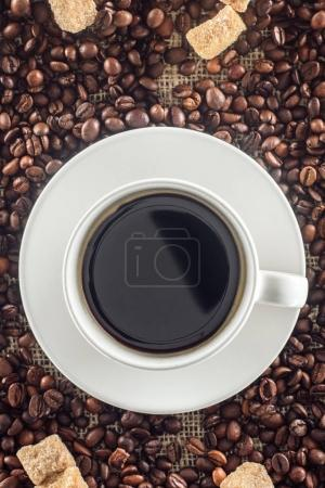 Photo for Top view of cup of coffee, roasted coffee beans and brown sugar on sackcloth - Royalty Free Image