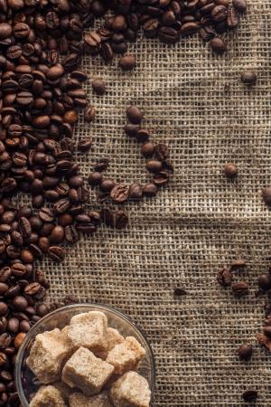 top view of roasted coffee beans with brown sugar in glass bowl on sackcloth