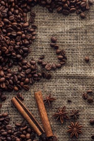 grains de café torréfiés avec bâtonnets de cannelle et anis étoilé sur sac