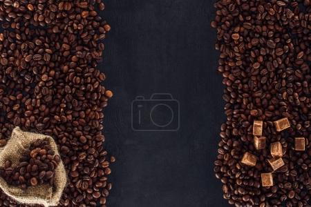 top view of roasted coffee beans with brown sugar and sackcloth on black