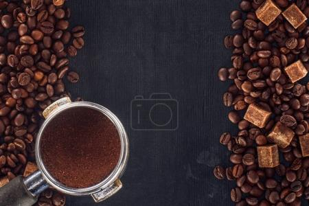 top view of roasted coffee beans with brown sugar and coffee tamper on black
