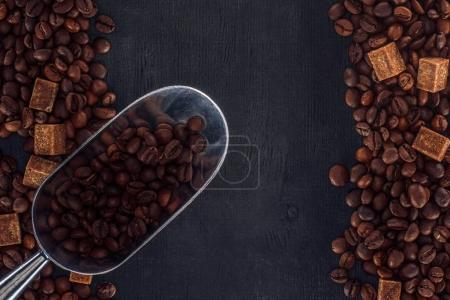 Photo for Top view of roasted coffee beans with brown sugar and scoop on black - Royalty Free Image