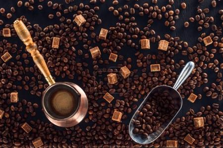 flat lay with roasted coffee beans, coffee brewer and metal scoop