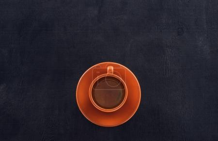 top view of cup of coffee with saucer on black