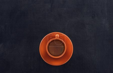 Photo for Top view of cup of coffee with saucer on black - Royalty Free Image
