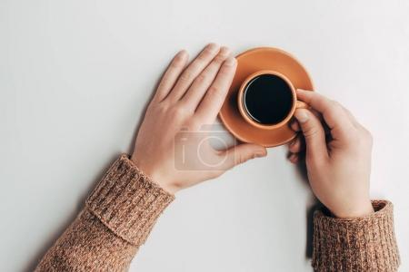top view of human hands and cup of coffee on grey