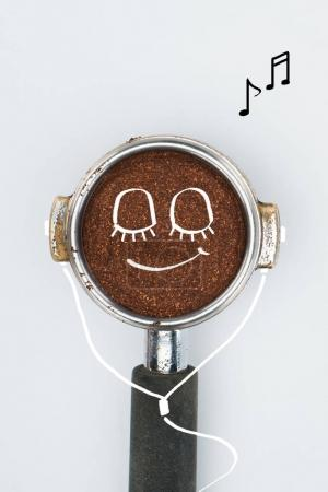 top view of coffee tamper with smiley face and earphones isolated on white