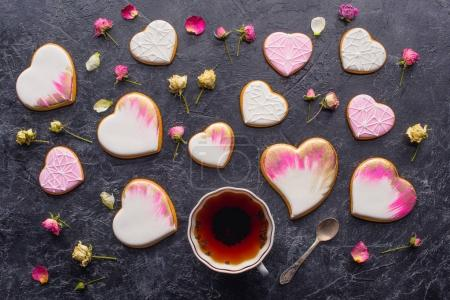 Photo for St valentines day flat lay with cup of tea, glazed heart shaped cookies and decorative flowers on dark tabletop - Royalty Free Image