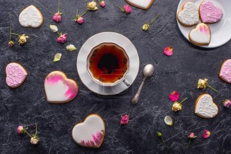 st valentines day flat lay with cup of tea, glazed heart shaped cookies and decorative flowers on dark tabletop