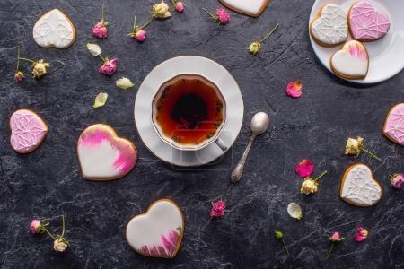 San Valentín plano con taza de té, galletas en forma de corazón acristalado y flores decorativas en la mesa oscura
