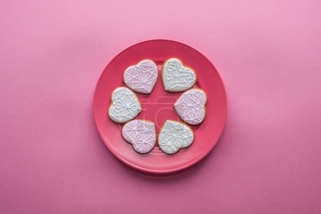 top view of sweet glazed cookies on plate isolated on pink, st valentines day holiday concept
