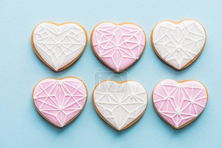 flat lay with arranged glazed heart shaped cookies isolated on blue, st valentines day holiday concept