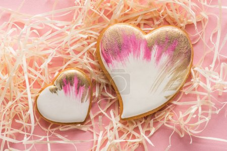 close up view of sweet heart shaped cookies and decorative straw on pink, st valentines holiday concept