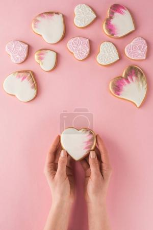 Photo for Partial view of woman holding glazed cookie in hands isolated on pink, st valentines day concept - Royalty Free Image