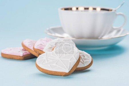 close up view of heart shaped cookies and cup isolated on blue