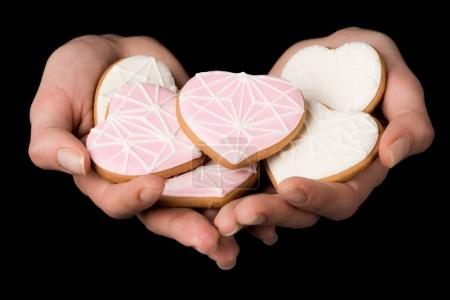 Photo for Close up view of female hands with glazed heart shaped cookies isolated on black - Royalty Free Image