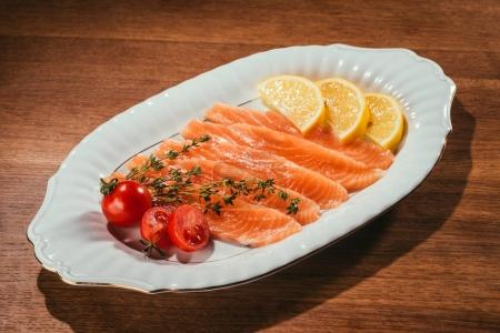 Salmon fish pieces with lemon, herbs and tomatoes on white plate on wooden table