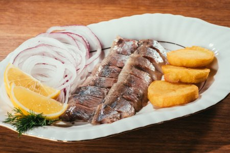 Herring fish pieces with lemon, onion and potato on white plate on wooden table