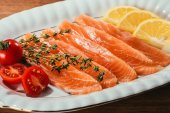 Close-up view of Salmon fish pieces with lemon, herbs and tomatoes on white plate